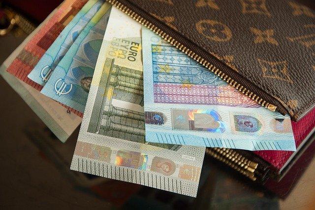 Peněženka, z níž vykukují bankovky