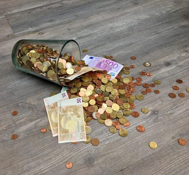 sklenice s rozsypanými penězi.jpg