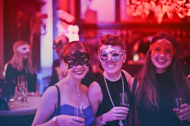 Tři dívky ve společenských šatech se škraboškami na očích