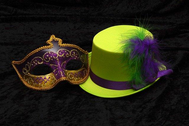Karnevalová maska a fialový cylindr ležící vedle sebe